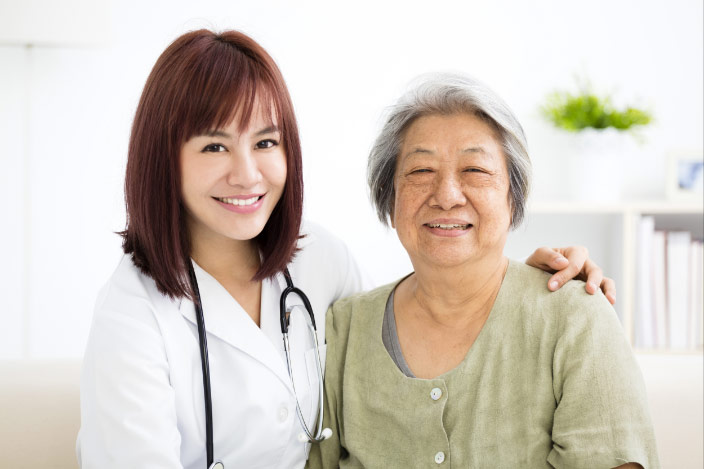 A doctor with her arm around an elderly woman
