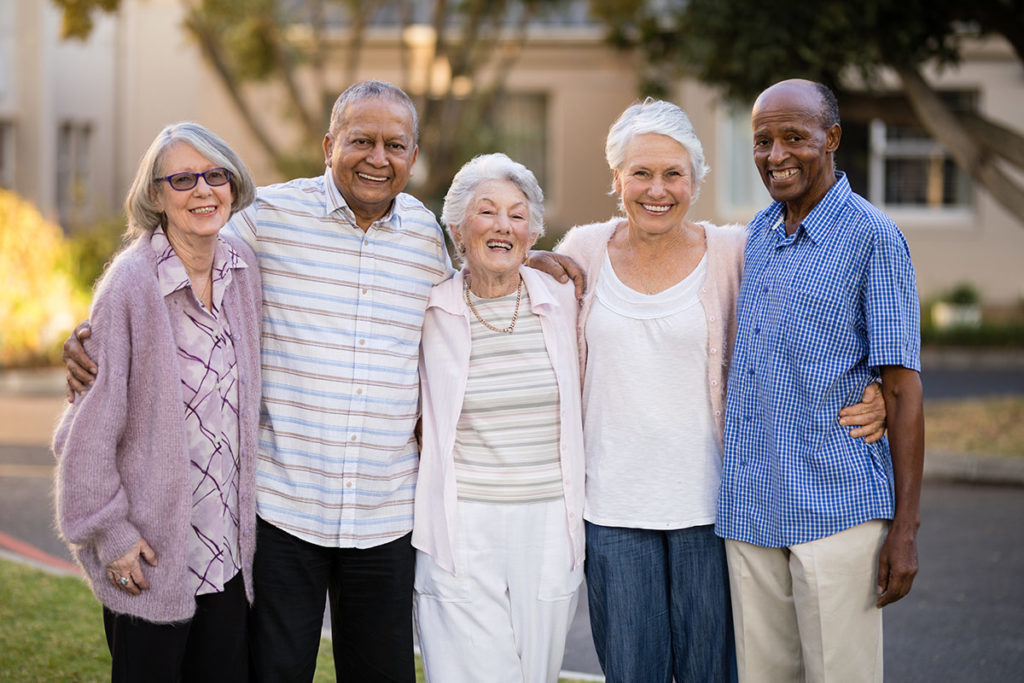 a photo of a diverse group of elder men and women standing closely together outdoors in what looks like a neighborhood