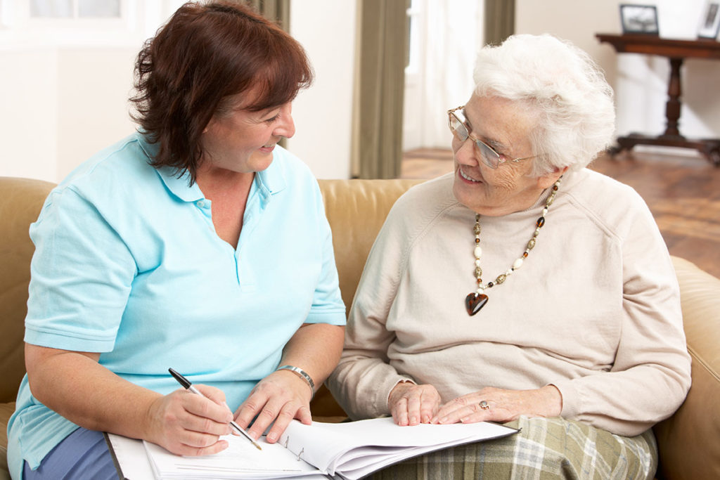 an image of a middle-aged woman helping her elderly mother fill out paper work as they both sit together on a couch inside a brightly lit room